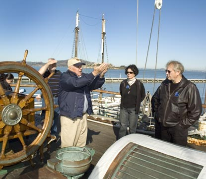 A volunteer near the stern of Balclutha talking with visitors.