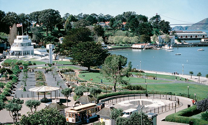 The Aquatic Park Historic District includes gardens, lawns, a cable car turnaround and lagoon. The Maritime Museum building is in the background and the Golden Gate Bridge is visible on the far right.