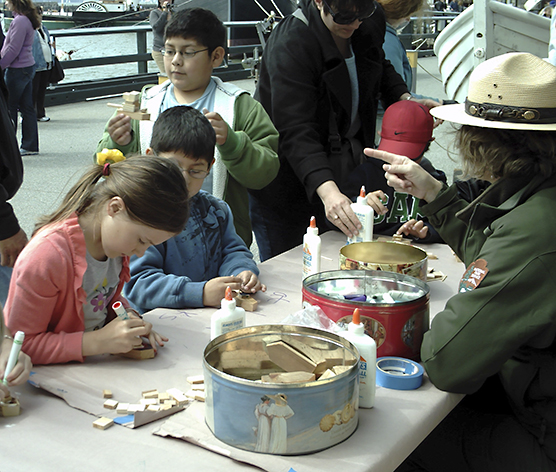 A park ranger with children at a table making crafts.