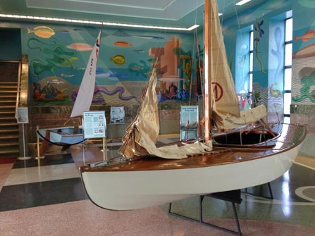 An exhibit of boats, text panels and colorful murals in the lobby of a building.
