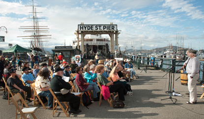 A group of people seated on Hyde Street Pier listening to two performers.