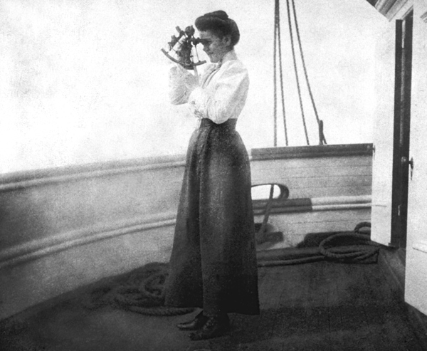 A woman standing on the deck of a ship and using a sextant.