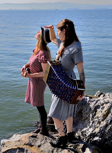 The musical duo Penny Opry: two women standing on a rock at the water's edge.