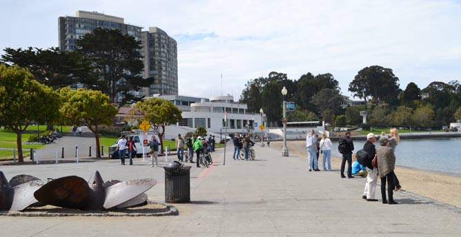 People standing on a cement walkway near the San Francisco Bay in Aquatic Park.
