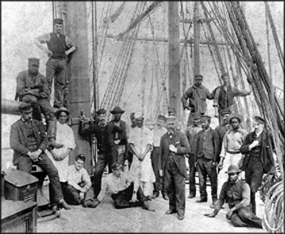 The crew of the British ship Rathdown photographed in San Francisco in 1892. The two men in aprons are the cook and steward, but the other black men are all seamen.