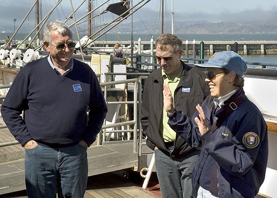 A woman who volunteers at the park speaking with two men aboard the historic sailing ship BALCLUTHA.