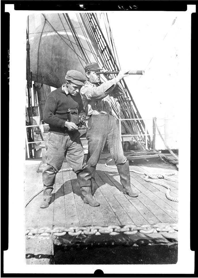 Two men standing on the deck of a ship.