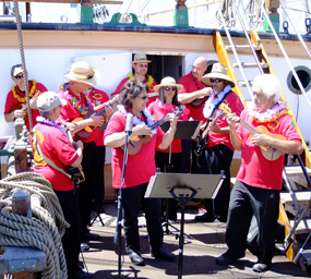 A group of musicians playing instruments on the main deck of BALCLUTHA.