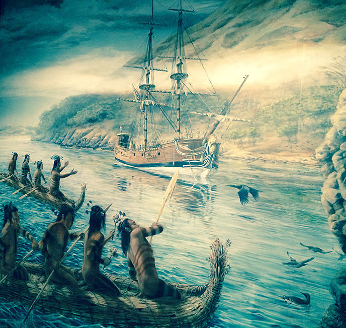 A painted mural depicting a sailing ship being greeted by men paddling tule reed canoes.