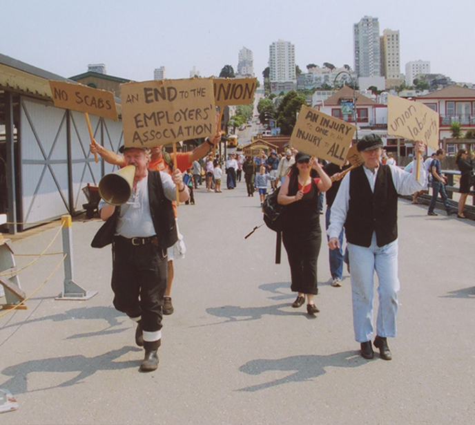 Living History players dressed in 1901-era clothing waking on the pier carrying signs.