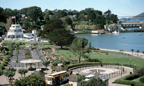 A view of the Aquatic park Historic District including the Maritime Museum, grass, beach and cove.
