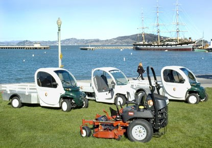 A photo of three small electric-powered utility vehicles and a ride-around lawn mower.
