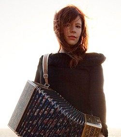 A woman standing and holding a button accordion.