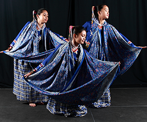 Three women dancers wearing blue garments.