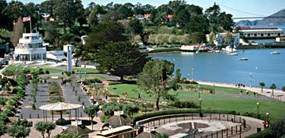 A view of the Aquatic Park Historic District which includes a lawn area, flowerbeds, benches, a promenade along the waterfront, and a spectacular view of the Aquatic Park lagoon and San Francisco Bay.