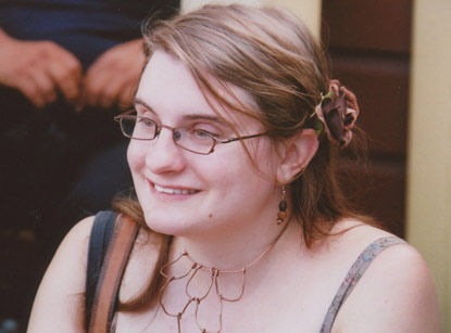 A woman wearing glasses and smiling.