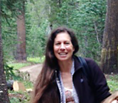 A woman standing on a path in the woods.