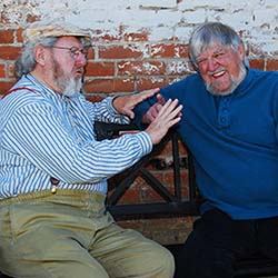 Two older men sitting against a red-brick wall talking and laughing.