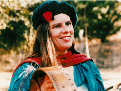 A woman wearing a black hat and holding a small drum.