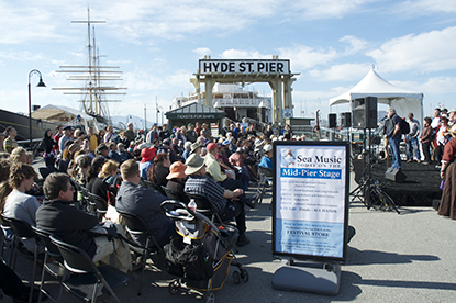 A crowd of people on Hyde Street Pier sitting on chairs and listening to music performers.