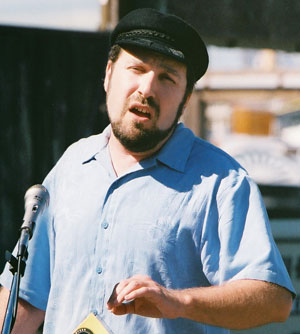 A man in a captain's cap singing.