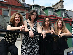 Four women standing next to each other and leaning on a railing.