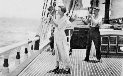 A woman standing on the deck of a 19th century sailing ship using a sextant to take a sight.