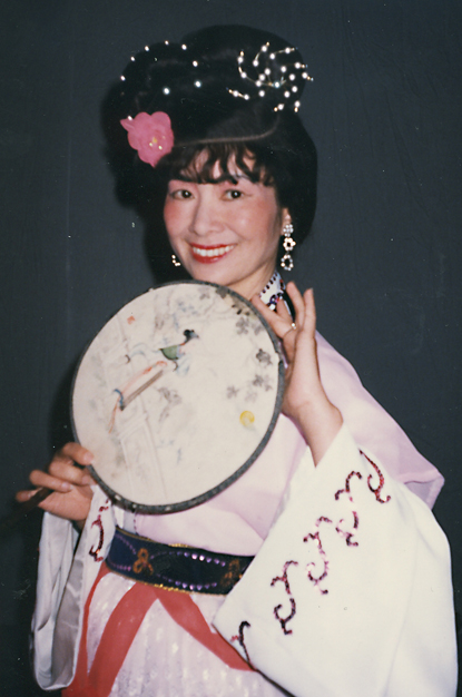 A woman holding a round fan.