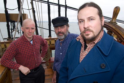 Three men standing on a ship.