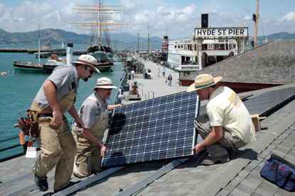 Park employees installing solar panels on the roof of a building on Hyde street Pier.