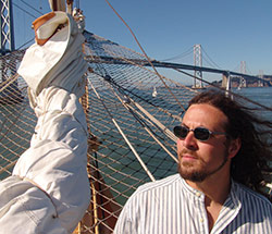 A man standing on a sailboat near the bow.