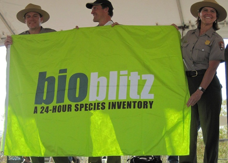 "Three people hold a flag with text ""bioblitz: a 24-hour species inventory."""