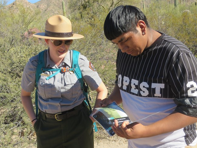 Ranger guides student through wildlife booklet during an in field educational program.