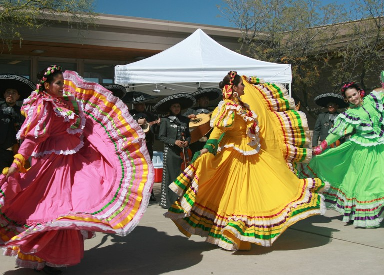 Women in brightly colored dresses swing their skirts.