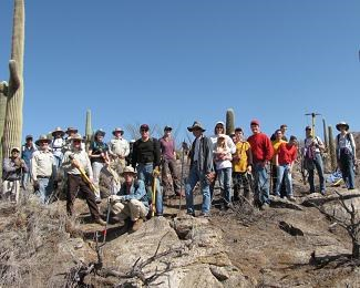 A group of people with tools and sun hats stand in a desert setting.