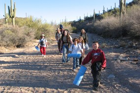 A group of children and a ranger walk with camping gear on a dirt trail in the desert.
