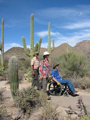 Three people, two walking one in a wheelchair, on a paved path in a desert setting.