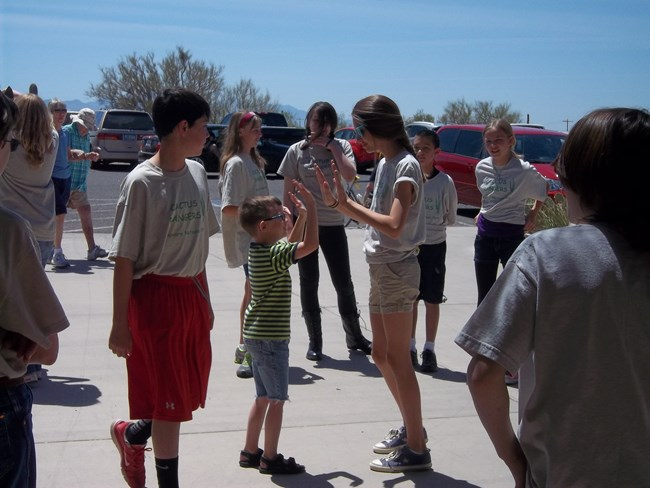 Jr Rangers demonstrate the movements of sun, earth, and moon in an eclipse at Saguaro National Park