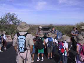 Rangers stand with a group of children and adults in hiking gear.