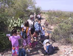 A group of students with a ranger sit and stand on a dirt trail in a desert setting.