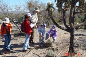 Four kids and a ranger look at a barrel cactus in a desert setting.