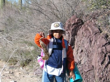 A child in hiking gear displays a seed pod for the camera in a desert setting.