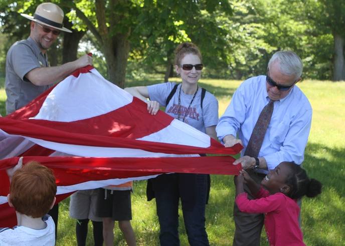 Students, teachers, and a park ranger fold a flag.