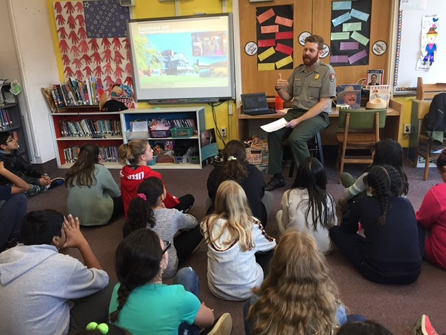 A park ranger speaks to a group of children in a classroom setting.