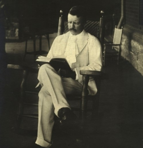 Theodore Roosevelt reading a book on his porch in 1904.