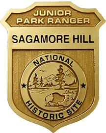 "A gold shield reading, ""Junior Park Ranger, Sagamore Hill National Historic Site."""
