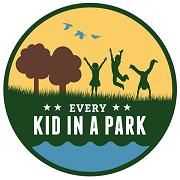 "Yellow circular logo with silhouetted children playing in a natural space with the words ""Every Kid in a Park"" printing underneath."