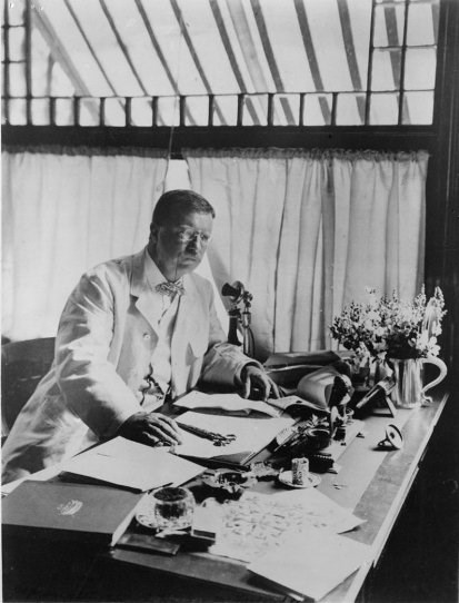 Theodore Roosevelt sits and works at the desk in his Sagamore Hill library.