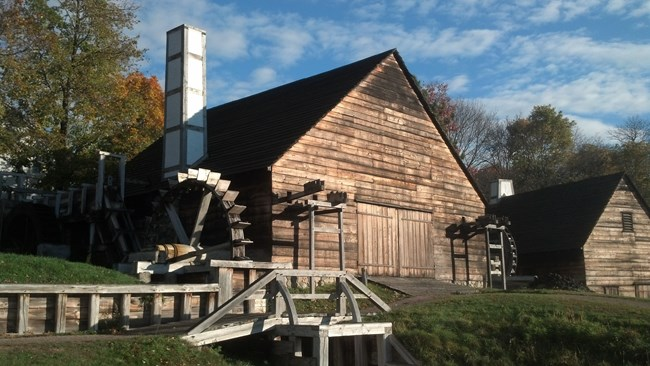 A wooden building with multiple water wheels and chimneys.