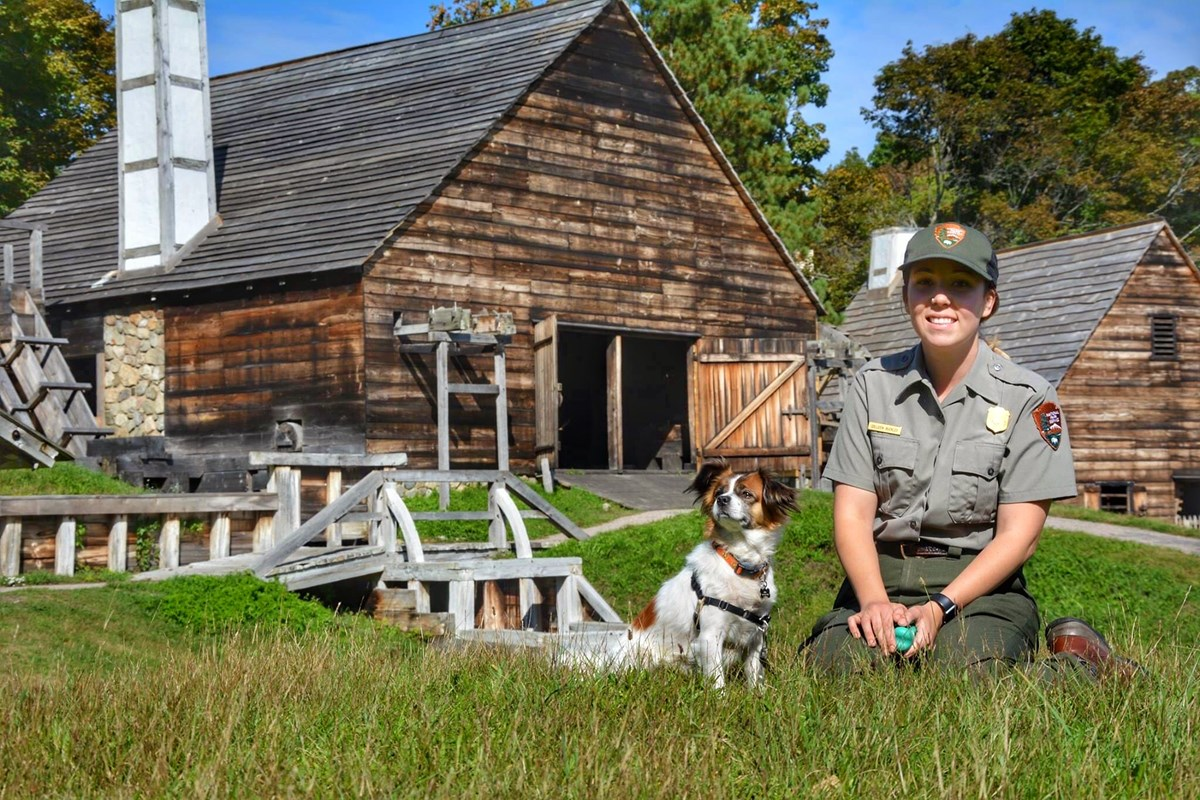female park ranger sits next to a dog in front of replica iron works buildings
